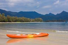 Orange Kajak auf dem Strand mit blauem Berg Lizenzfreies Stockbild