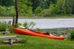 Orange Kajak auf den Ufern von einem kleinen See lizenzfreies stockfoto