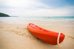Orange kajak på en strand. Fotografering för Bildbyråer