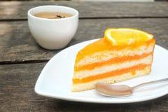 Orange kaka med varmt te fotografering för bildbyråer