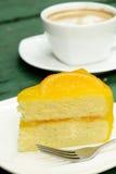 Orange kaka och varmt kaffe Arkivbilder