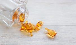 Orange kapslar för hud- och hårvitaminserum på den vita tabellen Arkivbilder