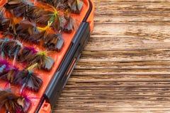 Orange Kasten mit Düsen für die Fischerei auf einem hölzernen Hintergrund lizenzfreie stockfotos