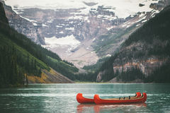 Orange Kayak in the Middle of the Lake Between Mountains during Daytime Stock Photo