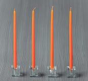 Orange Kerzen auf einem grauen strukturierten Hintergrund Lizenzfreie Stockbilder