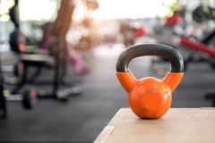 Orange kettlebell put on a wooden crate. stock photos