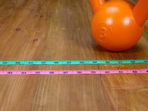 Kettlebell and measuring tapes. An orange kettlebell on a wooden floor, with two measuring tapes, pink and green Stock Image