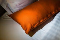 Orange Kissen auf Bett Lizenzfreie Stockfotos