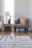 Orange Kissen auf modernem grauem Stuhl mit Nachttisch und Weiß stockfoto