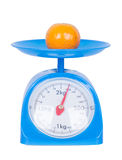 Orange on kitchen scale isolated on white background. With clipping path Stock Images