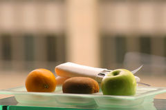 Orange, Kiwi Fruit and Apple. Orange, kiwi fruit and green apple on glass plate with silverware Royalty Free Stock Images