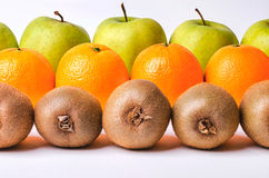 Orange, kiwi and apples in rows Royalty Free Stock Images