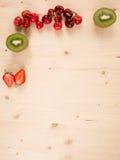 Orange, kiwi, cherry, strawberry on a wooden background Stock Images