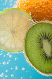 Orange, kiwi and lime in water with bubbles closeup Royalty Free Stock Photos