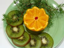 Orange and  kiwifruit. Fruit on a green plate Stock Image