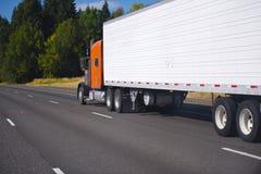 Orange klassisk halv lastbil och släp på huvudvägen Arkivbild