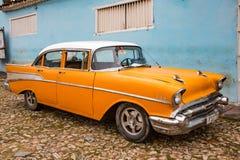 Orange klassiska Chevy parkeras framme av ett hem Arkivbild