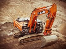 Orange Kliemt Excavator on Brown Soil Stock Images