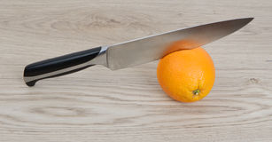 Orange with knife Stock Image
