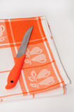 Orange knife on the orange tablecloth Royalty Free Stock Images