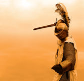 Orange knight background. Knight with a sword in mail shirt, armament and helmet (copy space Royalty Free Stock Photo