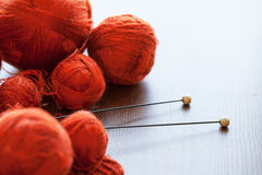 Orange knitwork with thread balls in a basket. Orange knitwork with thread balls and needles in a basket Royalty Free Stock Photography