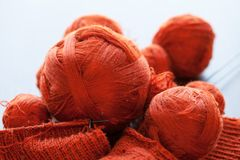 Orange knitwork with thread balls in a basket. Orange knitwork with thread balls and needles in a basket Stock Photos