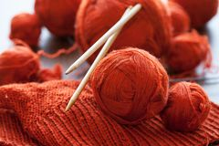 Orange knitwork with thread balls in a basket. Orange knitwork with thread balls and needles in a basket Royalty Free Stock Photo