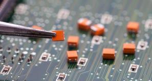 Orange kondensator för hacka med plattång royaltyfri fotografi