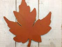 Orange konstgjord lönnlöv på wood bakgrund Fotografering för Bildbyråer