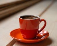 Orange kopp av nytt bryggat varmt kaffe på en trätabell Arkivbilder