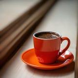 Orange kopp av nytt bryggat varmt kaffe på en trätabell Arkivbild