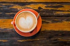 Orange kopp av varm lattekaffekonst på grungeyttersidatabellen Royaltyfri Bild