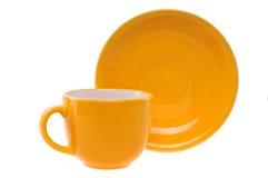 Orange kopp och tefat Royaltyfri Foto