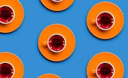 Orange kopp te på blå bakgrund Arkivfoto
