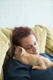 Orange Kätzchen der getigerten Katze, das im Schoss einer Frau schläft Lizenzfreies Stockfoto