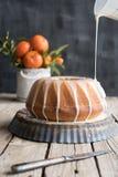 Orange Kuchen auf Holztisch und Dunkelheitshintergrund Lizenzfreies Stockfoto