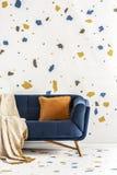 Orange kudde och filt på den blåa soffan i färgrik vardagsruminre med tapeten Verkligt foto arkivfoton