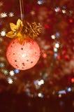 Orange Kugel mit Sternen und einem Kieferkegel. Vertikal Lizenzfreie Stockfotografie