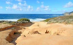 Orange kust och grovt hav Arkivfoto