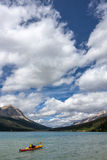 Orange Kyack in the blue water of Bow Lake near Banff Alberts Royalty Free Stock Photography