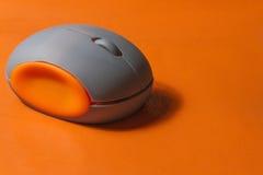 Orange läderbakgrund med den trådlösa musen Arkivbilder