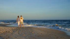 Orange län, Alabama/USA - Februari 15 2018: Par som går barfota innehavhänder på stranden på skymning arkivfilmer