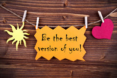 Orange Lable Saying Be The Best Version Of You. On Wooden Background Hanging On A Line, One Red Heart Symbol And One Yellow Sun Symbol Background Is Old Fashion Stock Images
