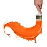 Orange Lack, der aus Pinsel heraus spritzt Stockfotografie