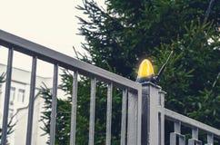 Orange lamp flasher on metal gates. Orange lamp flasher on big metal gates stock image