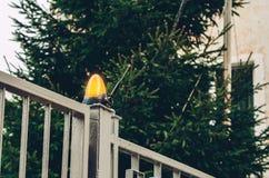 Orange lamp flasher on metal gates. Orange lamp flasher on big metal gates stock images