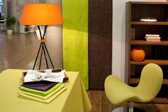 Orange lamp with green chair. Interior of living room, with two cups, green chair and orange lamp stock images