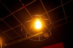 Orange lamp in a round steel frame hanging on the ceiling. Amp orange in a steel frame round shape stock photo