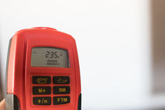 An orange laser meter pointed to the roof measuring 2.35 meters. Stock Photos